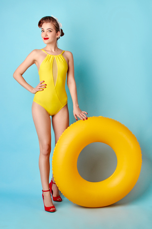 blonde in a bathing suit and with an inflatable circle on a blue background