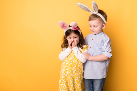 children with bunny ears on a yellow background Stockfoto