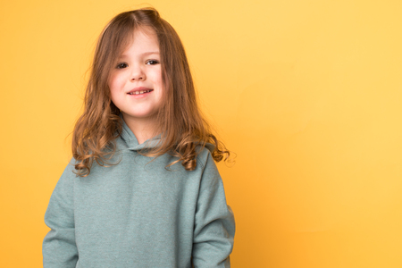little girl with curly hair on a yellow background
