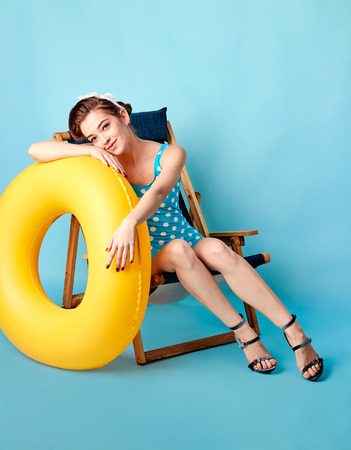 girl in a bathing suit lying on a lounger and holding in her hands an inflatable circle on a blue background