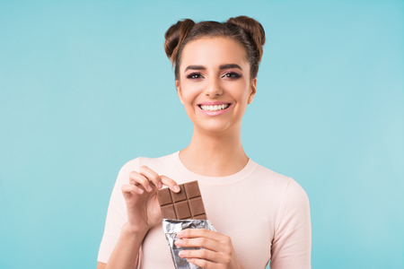 beautiful brunette with a chocolate in her hands on a blue background