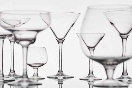 empty wine glasses of different shapes on a white background