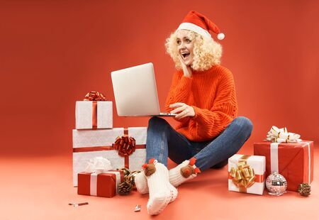 blonde girl with laptop surrounded by gift boxes