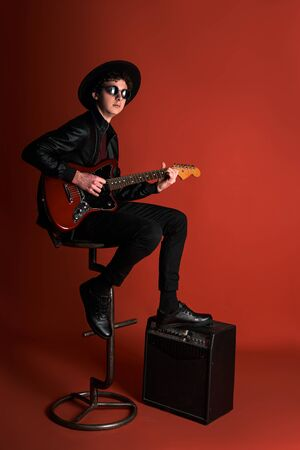 young musician sits on a chair with a guitar Stockfoto