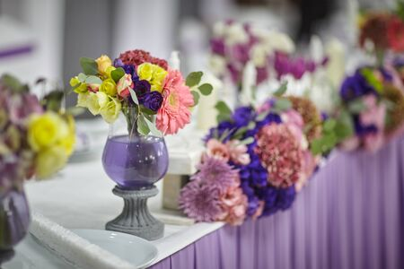 bouquets of various flowers as a decoration on wedding tables in a restaurant