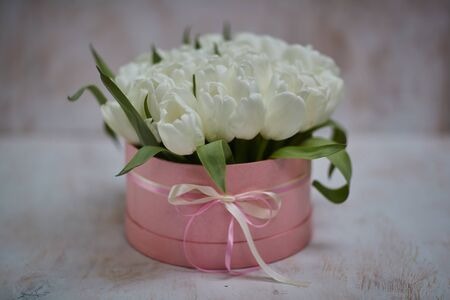 bouquet of white tulips in a pink box