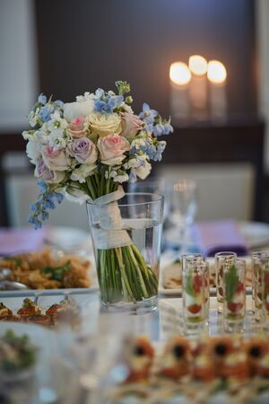 bouquets of various flowers as a decoration on wedding tables