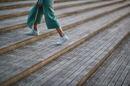 girl in white sneakers and pants walking on the stairs Reklamní fotografie
