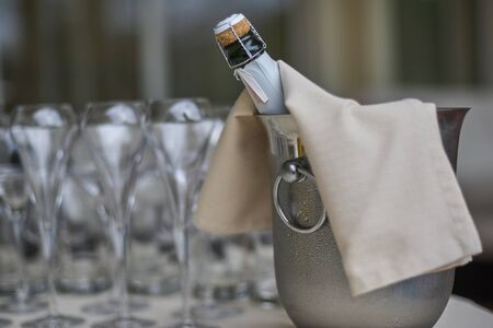 a bottle of champagne in a bucket with ice and glasses