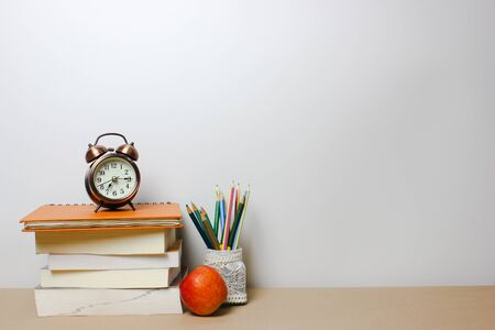 Back to school concept. Book clock and pencil on isolated white background. Copy space.