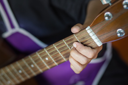 social actions: Closeup of fingers from playing acoustic guitar