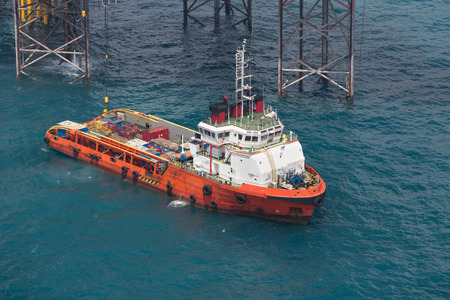 Supply vessel during operation along side with a drilling rig. Coast of Thailand