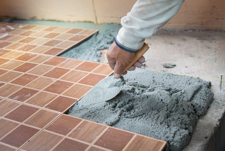 tiling: floor tiling by manual worker Stock Photo