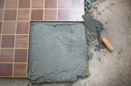 work from home: Home improvement, renovation construction trowel with cement mortar for tiles work, tile floor adhesive
