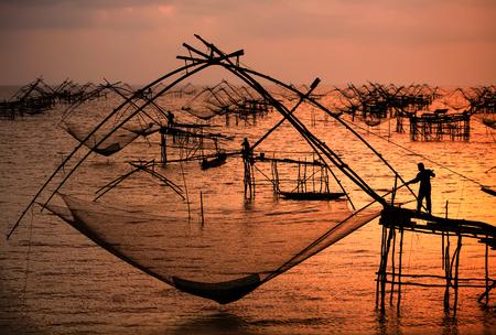 pescador: silueta de pescador con la salida del sol de fuego en el fondo