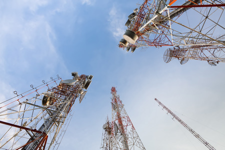 telecommunication: low angle view of two telecommunications towers against the sky Stock Photo