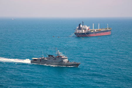 tanker ship: Aerial front side view of oil tanker ship sailing on open sea with battle ship Stock Photo