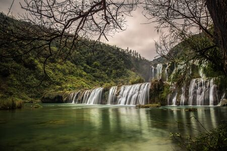 waterfall with sky: Waterfall in forest with cloudy sky