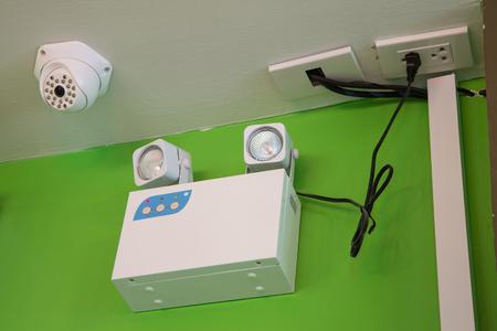 salidas de emergencia: Las luces de emergencia con dos lámparas y cámaras de seguridad CCTV en la pared