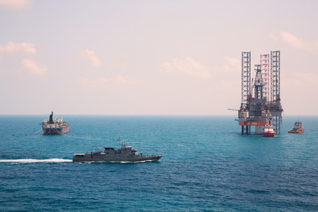 tanker ship: Oil rig and oil tanker ship with patrol vessel sailing pass in the gulf Stock Photo