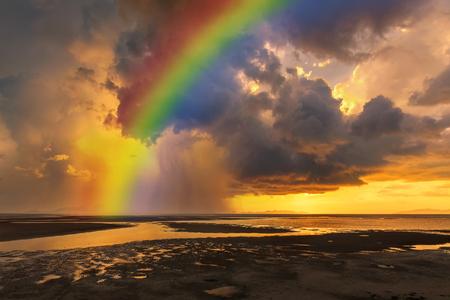 Zonsondergang met regenboog en regenachtig over het strand. Stockfoto