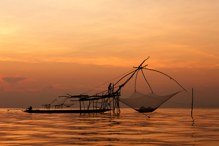 Asian fisherman on wooden boat casting a net for catching freshwater fish in nature river in the early morning with sunrise Stock Photo