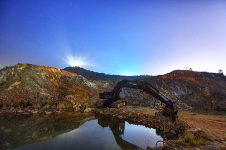 Excavator machine in construction site on night sky background