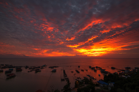 Sunset with dramatic sky over fishing village on the lake