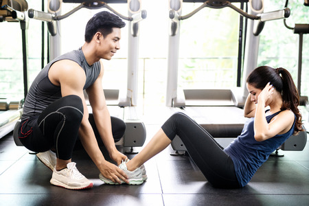 Man and women working out in gym together