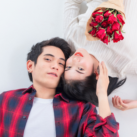Top view of happy young couple looking at camera each other and smiling while lying on floor