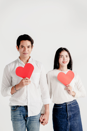 Happy young couple is holding red paper hearts 版權商用圖片