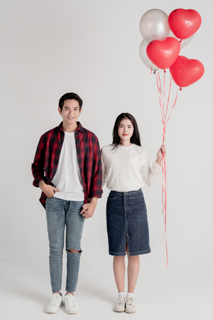 couple posing on grey background with balloons heart. Valentine's day 版權商用圖片