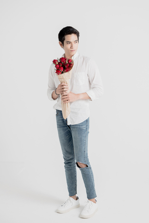 Full length portrait of a young handsome man carrying a flower bouquet and ready to meet his date