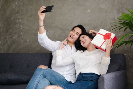 Beautiful young couple is holding gift box,doing selfie and smiling while celebrating at home