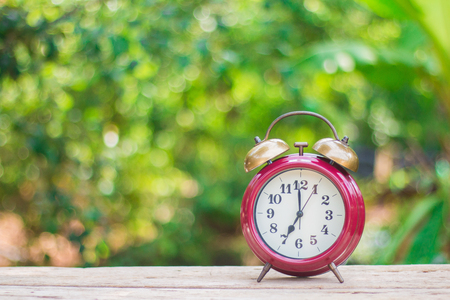 An antique red alarm clock on a wooden floor with a green background in the morning. Stock Photo