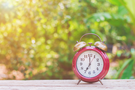 second floor: An antique red alarm clock on a wooden floor with a green background in the morning. Stock Photo