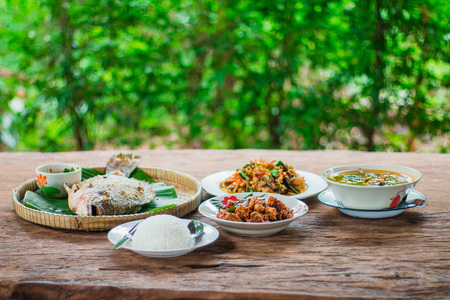 sauteed: Thai food, with fish and Thai food with fish With rice, burned spicy sauteed fish paste on a wooden table.