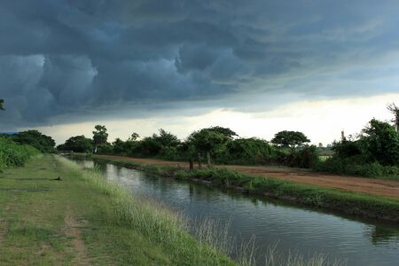 rainclouds: Rainclouds approaching above the canal Stock Photo