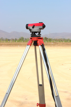 tachymeter: Level-measuring instrument  on tripod at construction site. Stock Photo
