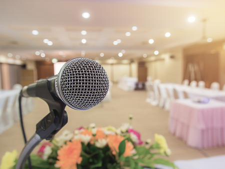 lecturing hall: Microphone in concert hall or conference room with defocused bokeh lights in background. Extremely shallow dof. Stock Photo