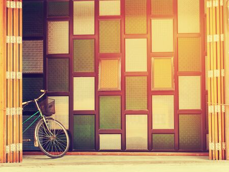 Vintage style photo of the retro bicycle standing  between colourful antiques windows  and wooden folding door. Copy space for insert text. photo