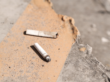 the thrown: cigarette butt thrown on the pavement with day light and vintage color effect.