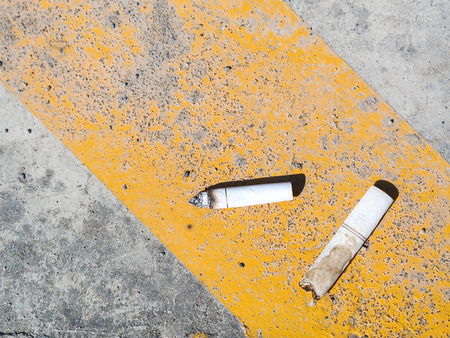 soil pollution: cigarette butt thrown on the pavement with day light.