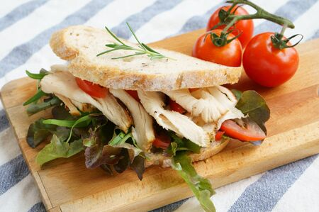 Grilled chicken sandwich with lettuce and tomato on wooden plate. Standard-Bild - 133638231