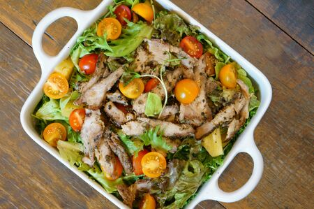Grilled pork salad with lettuce and tomato on wooden table.