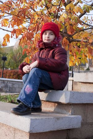 stitting: Girl with red hat at autumn