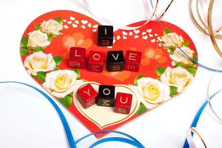 Words cubes over heart and ribbons photo