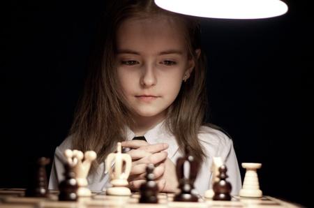 prodigy: Girl playing chess under lamp Stock Photo