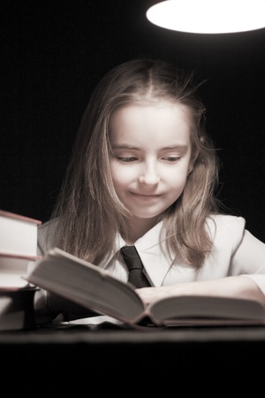 Girl reading book under lamp photo