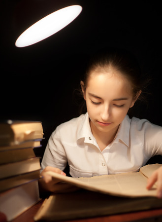 Young girl reading book at night dark at library under table lamp photo